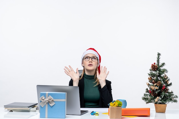 Exhausted business woman with santa claus hat sitting at a table with a xsmas tree and a gift on it in the office on white background