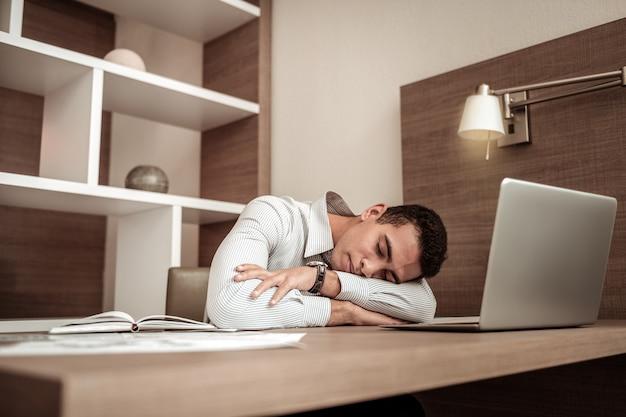 Измученный бизнесмен. занятый измученный бизнесмен засыпает на своем рабочем столе после целого дня работы