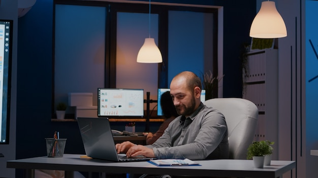 Exhausted businessman checking marketing statistics on laptop computer working in startup company office