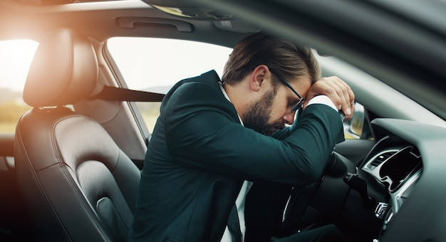 Exhausted businessman resting or sleeping on steering wheel staying in car somewhere in countryside