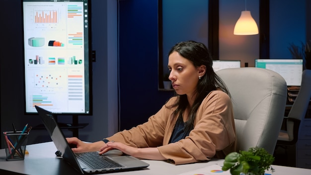 Exhausted businesswoman analyzing marketing statistics on laptop computer working in startup business company office. tired workaholic manager remains alone in financial room after his collegue left