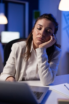 Exhausted businesswoman looking tired in camera sighing resting head in palm late at night in business office. focused entrepreneur using technology network wireless, working at marketing statistics