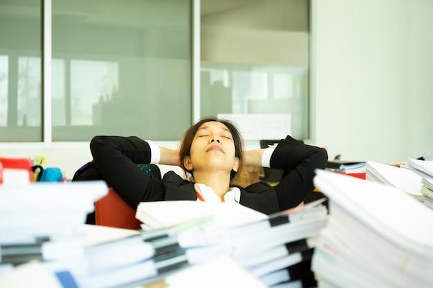 Paperwok의 더미와 함께 사무실에서 책상에서 자 고 지친 된 사업가.