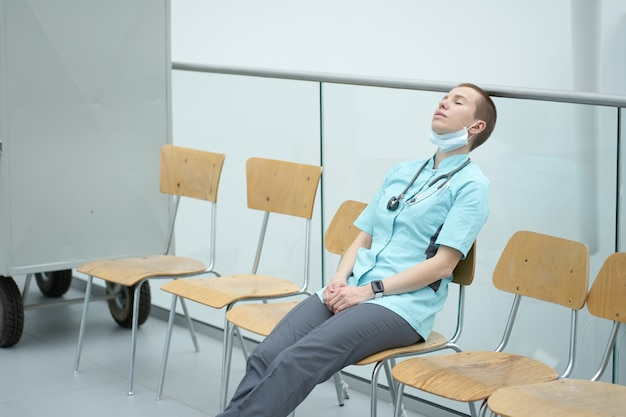 Exhausted caucasian female doctor sleeping at a work place after working overnight