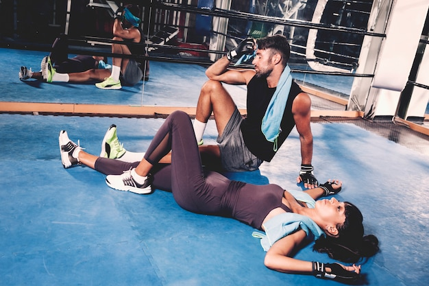 Exhausted couple on floor in gym