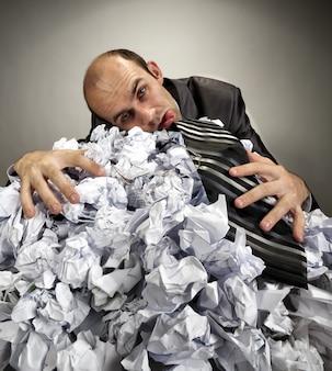 Измученный депрессивный бизнесмен, лежащий на мятых бумагах