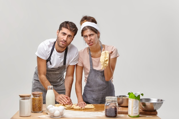 Exhausted displeased family couple have probelms with consistency of dough, cannot sculpt bun, wear aprons, spends lots hours at kitchen, have culinary failure. restaurant workers prepare cake