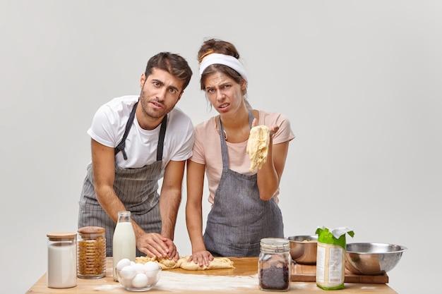 疲れ果てた不機嫌な家族のカップルは、生地の一貫性のあるプローブを持っており、パンを彫刻することができず、エプロンを着用し、台所で多くの時間を過ごし、料理の失敗をしています。レストランの労働者はケーキを準備します