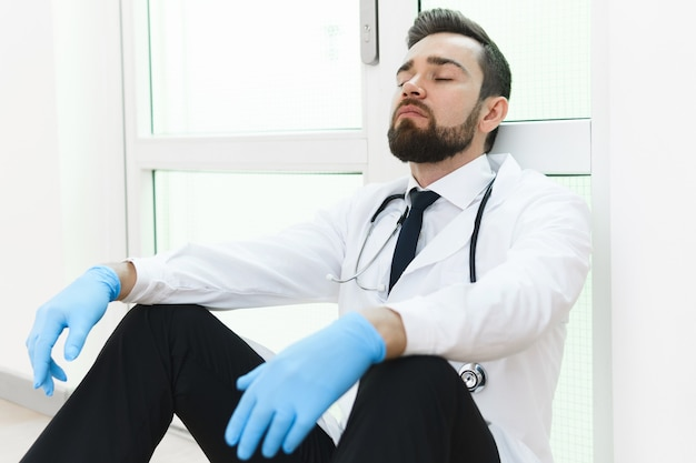 Exhausted doctor after very long shift in the hospital