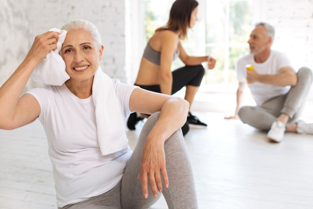 Exhausted elderly sportswoman sitting on the floor and leaning left arm on left knee while wiping her forehead