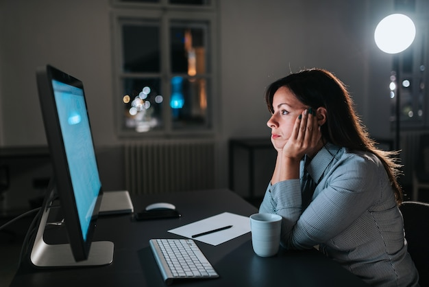 Exhausted entrepreneur looking at computer screen.