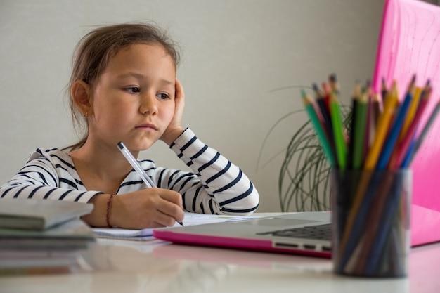 Изможденная этническая девушка смотрит на экран ноутбука и делает заметки в блокноте во время онлайн-урока дома