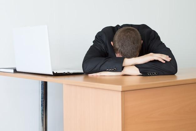 사무실 내부에 노트북과 나무 책상에 기대어 지쳐 임원 남자.