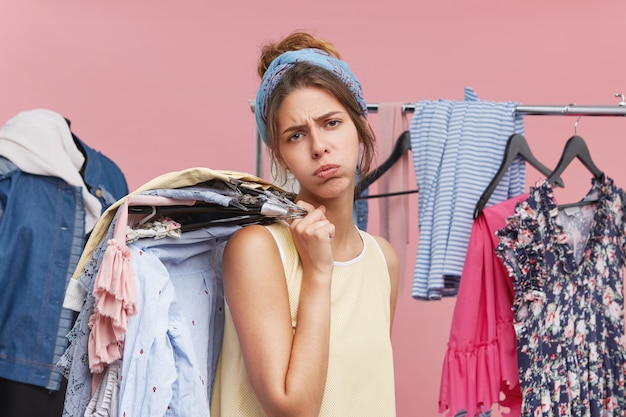 Exhausted female model blowing cheeks and having tired expression while standing in fitting room, holding hangers with clothes on shoulder, frowning face with dissatisfaction. tiredness and shopping