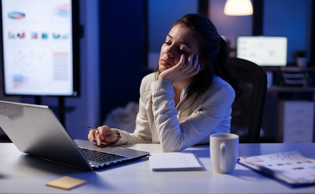 Exhausted freelancer falling asleep in front of laptop checking financial reports in company office late at night
