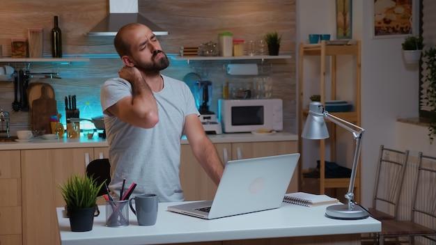 夜遅くに締め切りに取り組んでいる間、首を伸ばしている疲れ果てたフリーランサーの男。仕事の読み取り、書き込み、検索のために残業をしている最新のテクノロジーネットワークワイヤレスを使用している忙しい集中従業員
