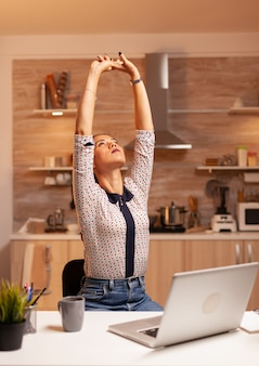 Exhausted freelancer woman streching while working on a deadline late at night. employee using modern technology at midnight doing overtime for job, business, busy, career, network, lifestyle ,wireles