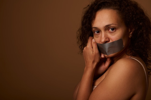 입을 막고 지친 겁에 질린 여성은 문자를 위한 공간이 있는 어두운 베이지색 배경에 옆으로 서서 카메라를 필사적으로 쳐다봅니다. 여성에 대한 폭력을 종식시키는 사회적 개념