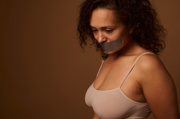 Exhausted frightened woman with sealed mouth looks desperately down, standing three quarters against a dark beige background with space for text. social concept of ending violence against women