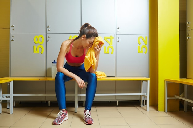 Exhausted girl in lockers room