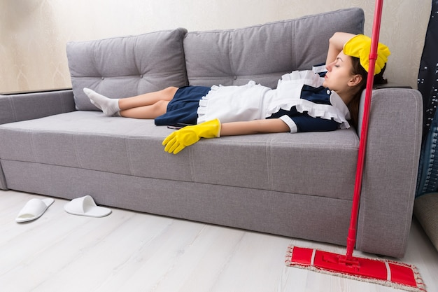 Измученная домработница отдыхает на работе, лежа на диване в униформе и дремлет со своей шваброй рядом