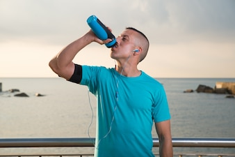 Exhausted male athlete drinking water outdoors