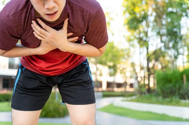 公園を走っているときに痛みを伴う狭心症または喘息の呼吸の問題に苦しんでいる疲れ果てた男性ランナーアスリート。