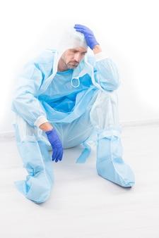 疲れ果てた男性医師の疫学者は、コロナウイルスpの安全保護衣装で頭痛を持っています