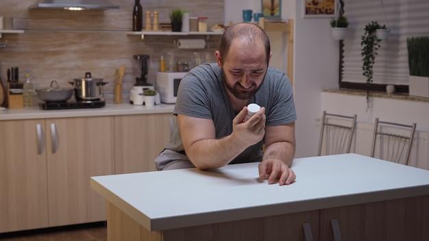台所に座っている錠剤のボトルを保持している疲れ果てた男。片頭痛、うつ病、病気、めまい症状で気分が悪くなる不安に苦しんでいるストレス、疲れた不幸な心配している体調不良の人