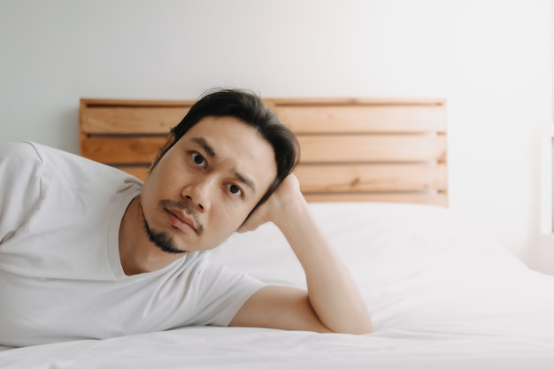 Exhausted man lay on the bed as he feels burnout