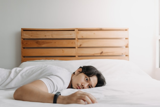지친 남자는 지친 기분으로 침대에 누워 있다