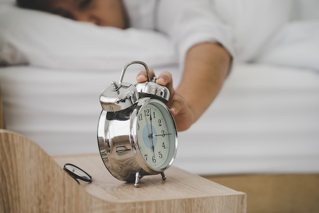 Измученный мужчина, спящий в постели, устал просыпаться по утрам под звон будильника и страдает бессонницей.