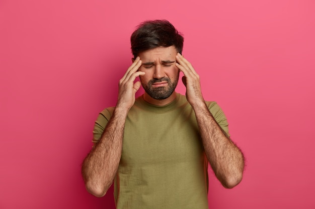 Exhausted man touches temples with closed eyes, suffers from headache, waits someone bring painkillers, wears t shirt, has bad day, isolated over pink wall, bothered with painful disease