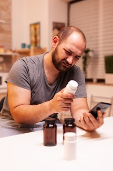 Exhausted man with headache holding bottle with painkillers while searching information on phone in kitchen. stressed tired unhappy worried unwell person suffering of migraine, depression, disease and