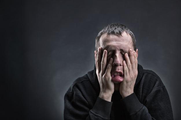 Измученный мужчина с ладонями на щеках