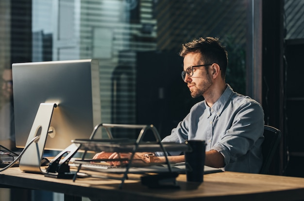 Exhausted man working overtime in office