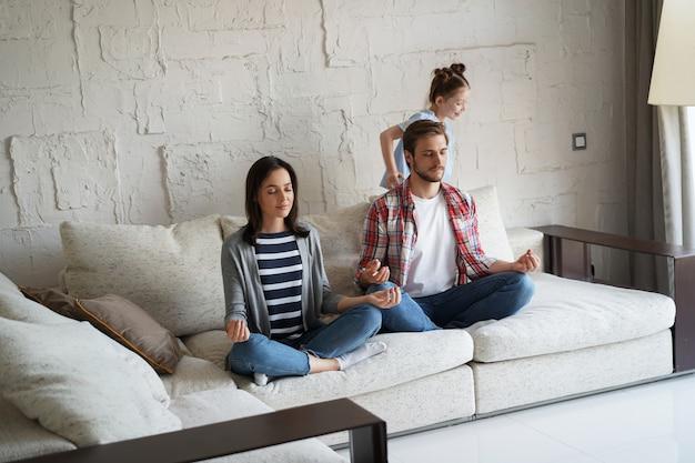 Измученные мать и отец, сидящие на диване, чувствуют себя раздраженными, усталыми, в то время как маленькая шумная дочка с криком бегает по дивану.