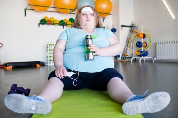 マットの上に座って疲れ果てた肥満女性