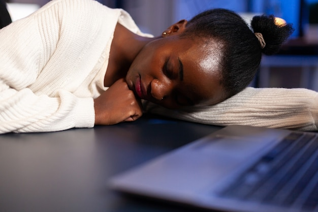 Exhausted overload african business woman falling asleep on desk with open laptop monitor while working in start up company