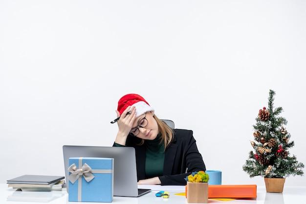 Donna bionda esausta e oberata di lavoro con un cappello di babbo natale seduto a un tavolo con un albero di natale e un regalo su di esso in ufficio su sfondo bianco
