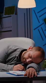 Exhausted overworked businessman sleeping on desk table in startup business office after analysing f...