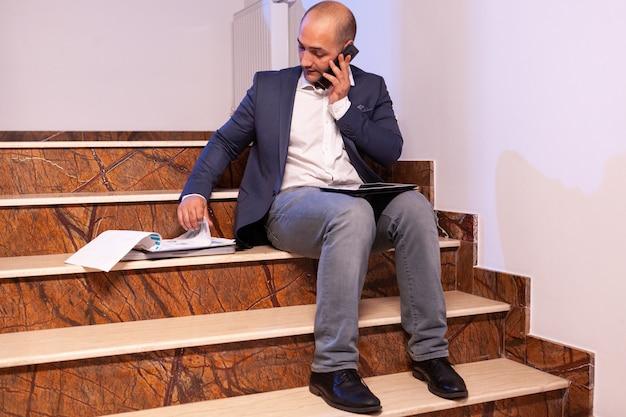 プロジェクトの締め切りについてチームと電話で話している疲れ果てた過労のビジネスマン。ビルのオフィスの階段に座っている企業の夜遅くに働いている起業家。