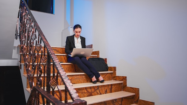 Exhausted overworked entrepreneur doing overtime on project deadline typing on laptop. serious entrepreneur working on corporate job sitting on staircase of business building late at night.