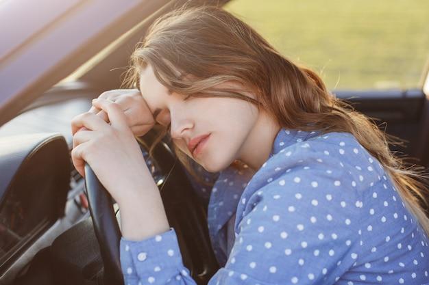 지친 과로 한 여성 운전자는 더 이상 차를 운전할 수 없으며, 바퀴 달린 낮잠, 졸리고 피곤함, 두통이 있습니다. 피로 여자는 출퇴근 시간에 운전 후 피곤합니다. 피로와 운전 개념