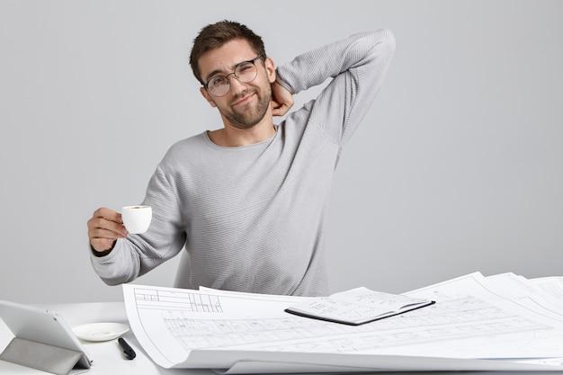 Architetto maschio oberato di lavoro esausto si siede alla scrivania, si allunga e beve caffè espresso