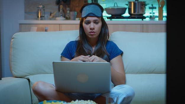 ソファに座って自宅からラップトップを使用して同僚とウェブカメラで話している疲れた人。インターネット技術を使用して夜にノートブックコンピュータでビデオ通話をしているアイマスクを持つパジャマの女性