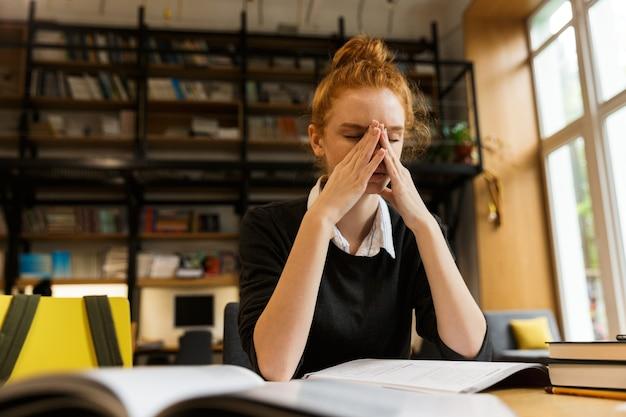 Измученная рыжая девочка-подросток учится за столом