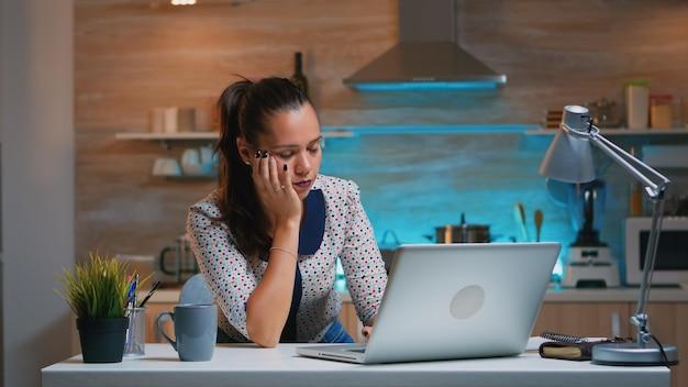 지친 원격 여성이 밤에 부엌에 앉아 노트북 작업을 하며 잠에서 깨어나 의자에서 낮잠을 자고 있습니다.
