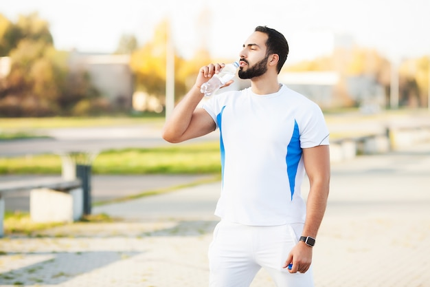 Exhausted runner man drink water on the park after workout
