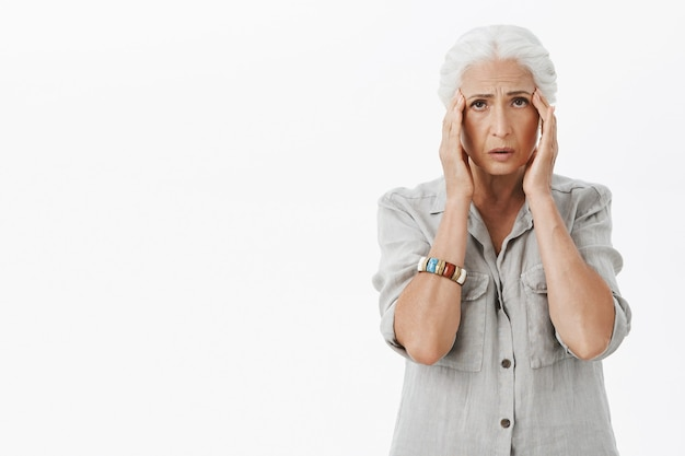 Exhausted sad grandmother touching head, complaining headache, have migraine